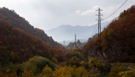 autumn forest and mountains in the fog in bad weather in prata sannita with electricity pylons Stock Photo