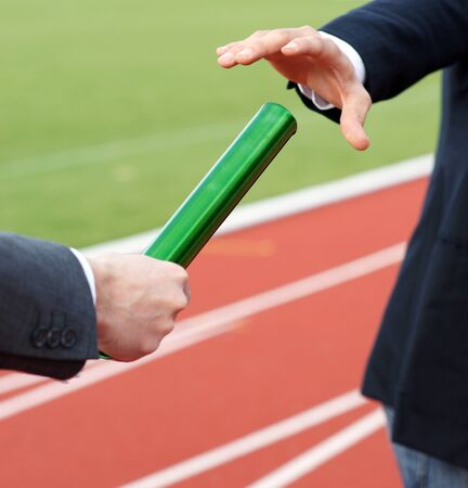 Businessmen passing baton in relay race