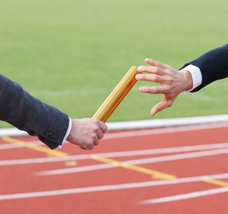 Businessman passing baton in relay race