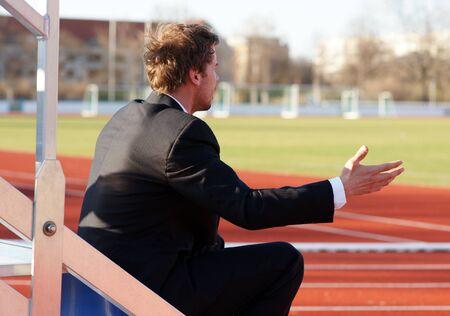 Trainer sitting in stadium next to the running track - upset gesture lack of understanding