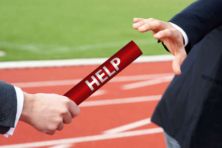 Give or accept help - businessmen pass baton in relay race in stadium