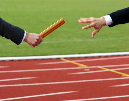 Businessmen pass on the baton in relay race in stadium