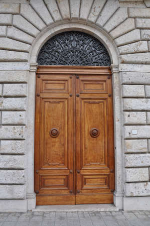 Wooden door and a stone wall, buildings Tuscany