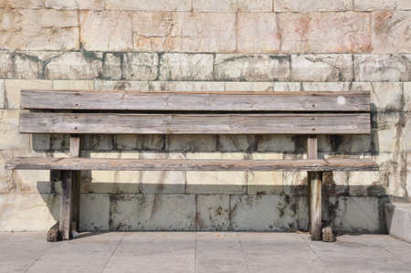 absence: Bench against the wall, loneliness and absence Stock Photo