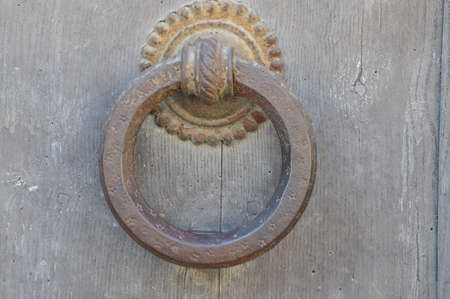 Round steel knocker on wooden door photo
