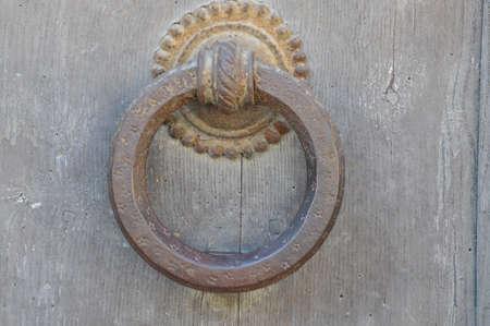 Round steel knocker on wooden door photo