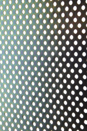 Shiny metal plate background with symmetrical holes photo