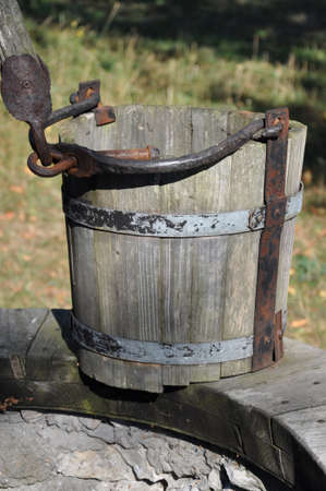 Wooden empty bucket at the well, a symbol of drought and poverty Stock Photo - 15229719