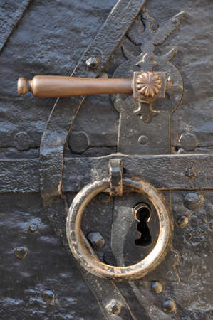 Handle and knocker on the forged steel door photo