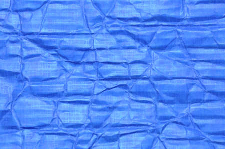 Creased blue carton surface, folded paper  photo
