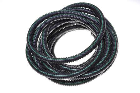 Ribbelbuis voor elektrische kabels opgerold in een cirkel op wit wordt geïsoleerd