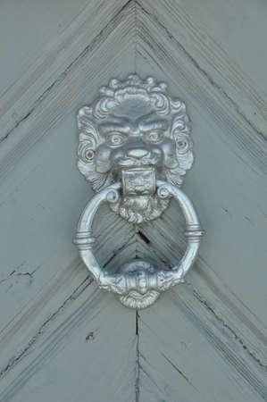 Lion head knocker on wooden door photo