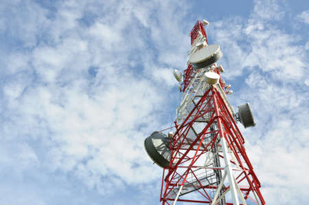 Tower with cell phone antenna system against blue sky