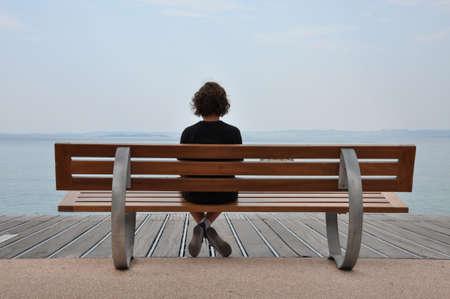 海の岸でベンチに座って孤独ティーンエイ ジャー