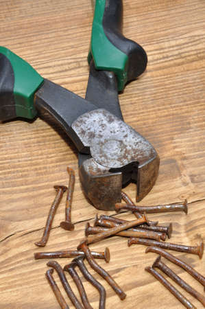 Old rusty pliers and nails on a wooden table photo