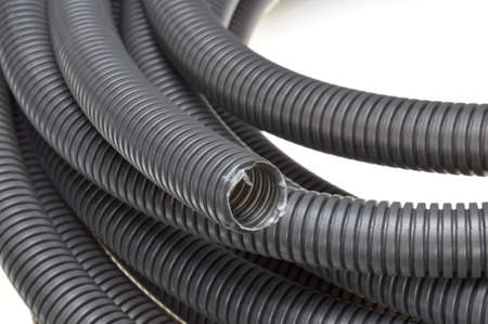 Black corrugated pipes isolated on white background photo