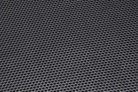 Metal surface with holes, industrial background photo
