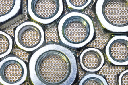 shiny metal background: Shiny nuts on metal surface abstract background