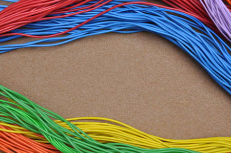 felt: Color cables on brown felt as background Stock Photo