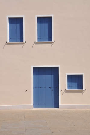 Closed blue windows and door on wall of mediterranean house during the siesta time Stock Photo