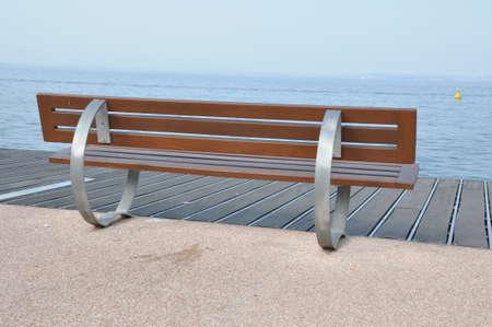 lakeshore: Empty bench on the lakeshore of Lake Garda, Bardolino, Italy Stock Photo