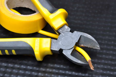electrical parts: Pliers with electrical cable on metal background