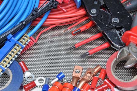 electricista: Herramientas eléctricas, componentes y cables en la superficie de metal