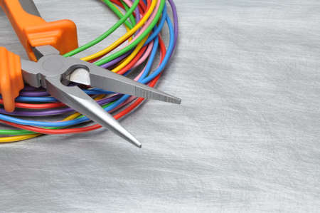 Tools for electrician and cables on gray metal surface