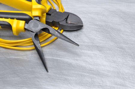 electricista: Herramientas y cables en la superficie de metal con lugar para el texto eléctricas amarillas Foto de archivo