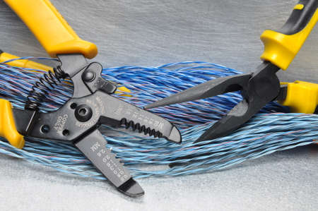 Crimping tool pliers and cables on gray background with place for text