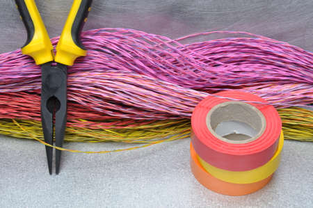 electricista: Multicolored pliers, insulating tapes and cables on metal surface