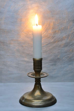 glow stick: Lighted candle in an old candlestick on gray background