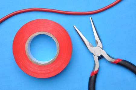 cable cutter: Tools for electrician pliers, insulation tape and cable on blue background