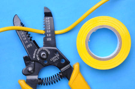stripper: Wire stripper, insulation tape and cable on blue background Stock Photo