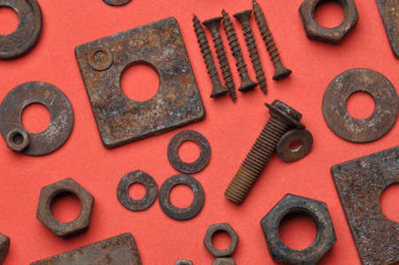 background red: Old rusty screw bolts and nuts on red background Foto de archivo