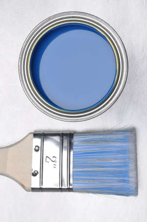 paint can: Top view of blue paint can with brush on gray metal background