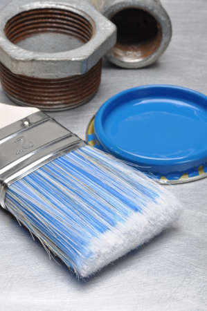 paint can: Blue paint can lid with brush and metal plumbing parts on gray metal background Stock Photo