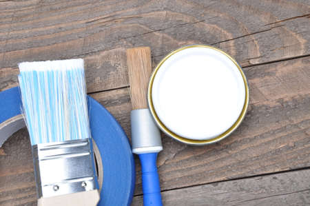 masking tape: Can of white paint brush and masking tape on old boards