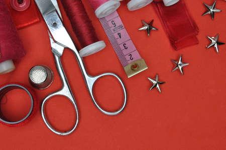 kit de costura: Costurero de herramientas, tijeras, hilo y accesorios sobre un fondo rojo