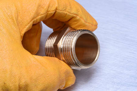 plumb: Hand in glove holds a plumbing part Stock Photo