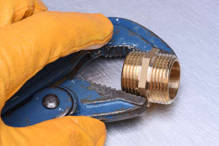 fitting in: Hand in glove holding a wrench and fitting brass part