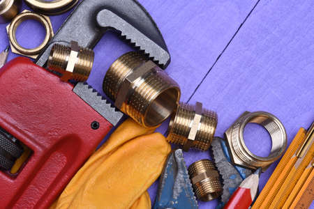 plumbing accessories: Tools and plumbing accessories on a wooden background Stock Photo