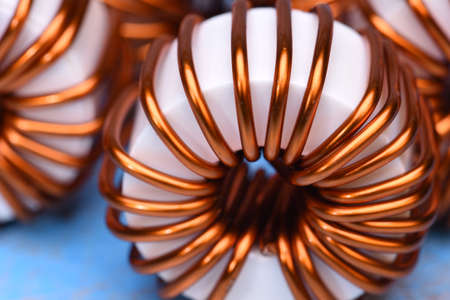 electromagnetism: Macro of a copper coils on blue background