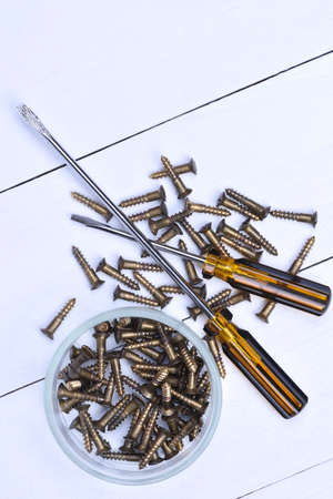 old metal: Box with brass screws and screwdrivers on wooden table