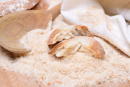 breading: Bread crumbs on wooden table with spoon