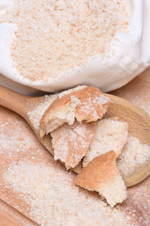 crumbing: Bread crumbs on wooden table with spoon