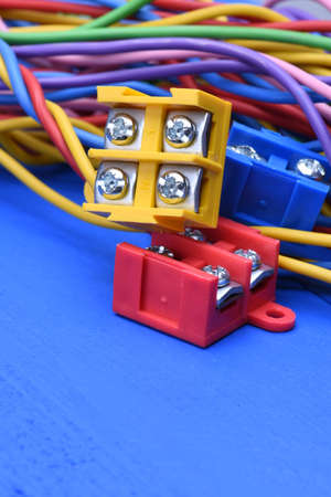 cables electricos: Color electric cables with terminal blocks on blue wooden background Foto de archivo