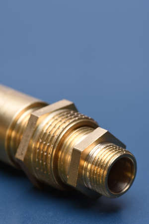 Brass fittings for water and gas on blue metal surface Stock Photo