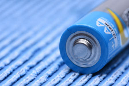 Single AA Battery Closeup Lying on Blue Background