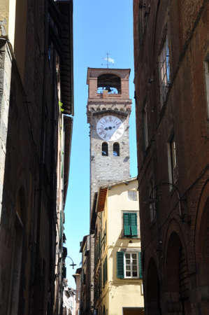 articles: Narrow street and high tower of Lucca town in Italy